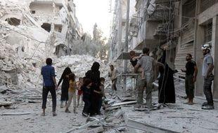 Une famille syrienne quitte un quartier qui vient d'être bombardé par les aviations russe et syrienne, le 23 septembre 2016, dans le nord d'Alep (Syrie).