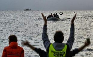 Des militants d'une ONG guident des migrants arrivant à bord d'un bateau arrivant de Turquie à Mytilène sur l'île grecque de Lesbos le 19 février 2016
