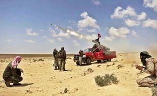 Des insurgés tirent sur des pro-Kadhafi, hier près de Brega.