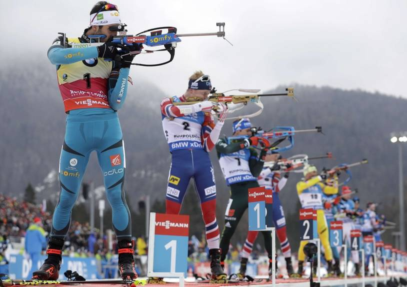 Winner Johannes Thingnes Boe of Norway, 2nd left, and second placed Martin Fourcade of France, left, shoot during the men's 15km mass start competition at the biathlon World Cup in Ruhpolding, Germany, Sunday, Jan. 14, 2018.
