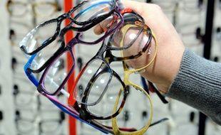 Photo d'illustration d'un opticien tenant des paires de lunettes dans sa main.