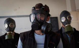 Des hommes portent des masques à gaz lors d'une simulation d'attaque chimique, dans le nord de la Syrie, en mars 2014
