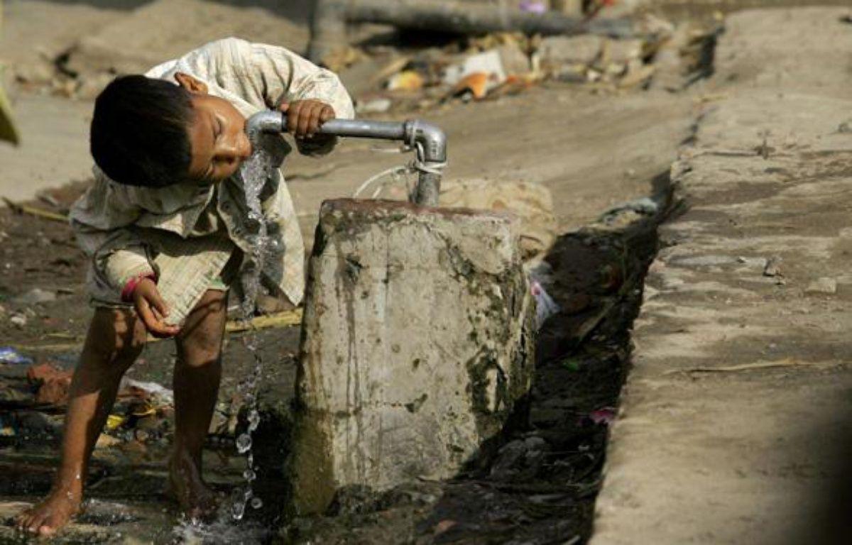 Un enfant boit de l'eau au robinet, en Inde, dans un quartier où l'eau potable n'arrive pas dans les maisons. – Altaf Qadri/AP/SIPA