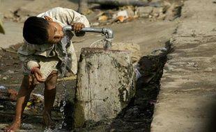 Un enfant boit de l'eau au robinet, en Inde, dans un quartier où l'eau potable n'arrive pas dans les maisons.