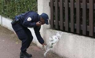 Un policier dépose des fleurs en hommage à ses collègues tués dans une attaque au couteau près de leur domicile à Magnanville, à l'ouest de Paris, en juin 2016.