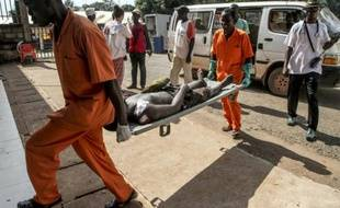 Une personne blessée, lors de violences provoquée par l'assassinat d'un conducteur de moto-taxi, arrive sur une civière à l'hôpital de Bangui, le 26 septembre 2015 en Centrafrique