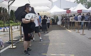 Pékin (Chine), le 19 juin 2020. Des Chinois patientent avant de subir un test pour savoir s'ils sont porteurs du coronavirus.