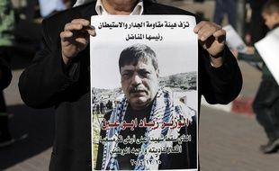 Un palestinien porte le portrait de  Ziad Abu Ain, mort le 10 décembre 2014.