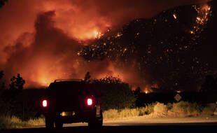 Un automobiliste face au feu de forêt qui brûle sur le flanc d'une montagne à Lytton, en Colombie-Britannique, le jeudi 1er juillet 2021.