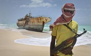 Un pirate somalien, le visage masqué, se tient devant un navire taïwanais, le 23 septembre 2012