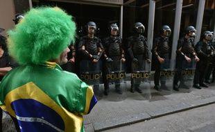 Un supporter brésilien devant la police anti-émeute, le 9 juin 2014, à Sao Paulo.