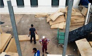 Des migrants se tiennent près d'un matelas près du centre d'hébergement temporaire de Lampedusa (Italie)le 8 octobre 2013