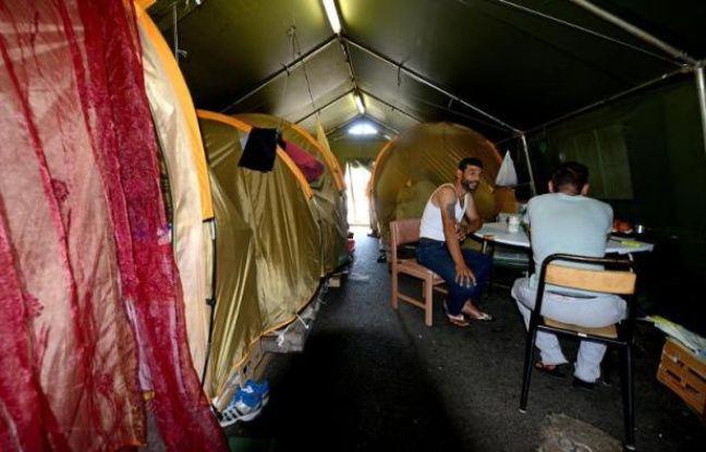 Des hommes dans un camp de fortune pour demandeurs d'asile, le 18 juillet 2014 à Grenoble