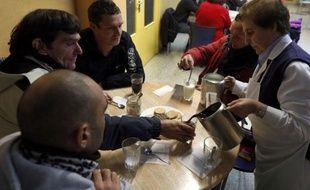 Sous la neige qui tombe pour la première fois de l'hiver, ils se pressent à l'entrée du centre d'accueil de Caritas à Burgos, dans le nord de l'Espagne. Immigrés, femmes, chômeurs, ils ont les multiples visages de la pauvreté qui grandit dans ce pays en crise.