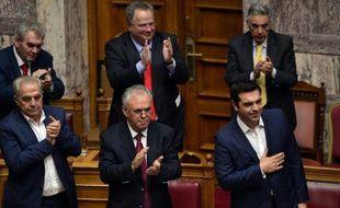 Le Premier ministre grec Alexis Tsipras (d) est applaudi par les membres du Parlement lors du vote de confiance au gouvernement, le 8 octobre 2015 à Athènes