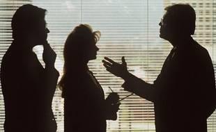 Deux hommes et une femme discutent dans un bureau.