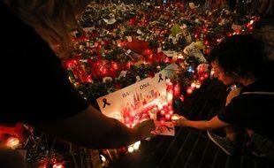 Des passants déposent bougies et cadeaux pour rendre hommage aux victimes des attentats de Barcelone et Cambrils.