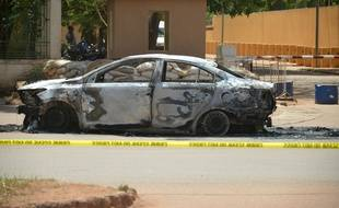 Cette photo prise le 3 mars 2018 à Ouagadougou montre une voiture incendiée devant l'ambassade de France, un jour après des attaques terroristes. AFP PHOTO / Ahmed OUOBA