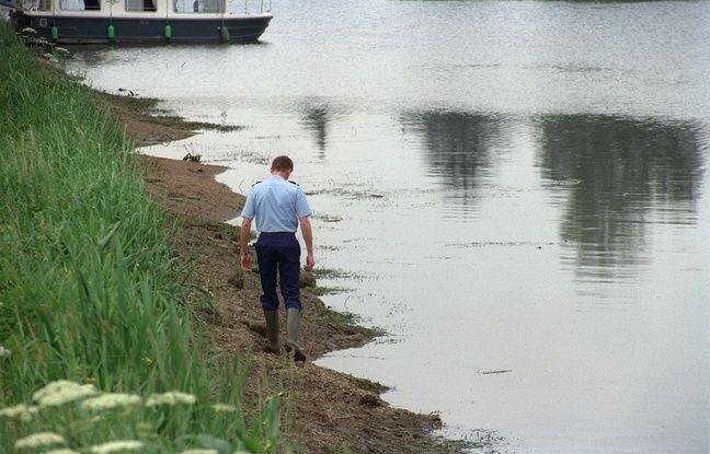 Monéteau (Yonne), le 19 mai 1990. Un policier cherche des indices sur les bords de l'Yonne où le corps de Joanna Parrish a été découvert.