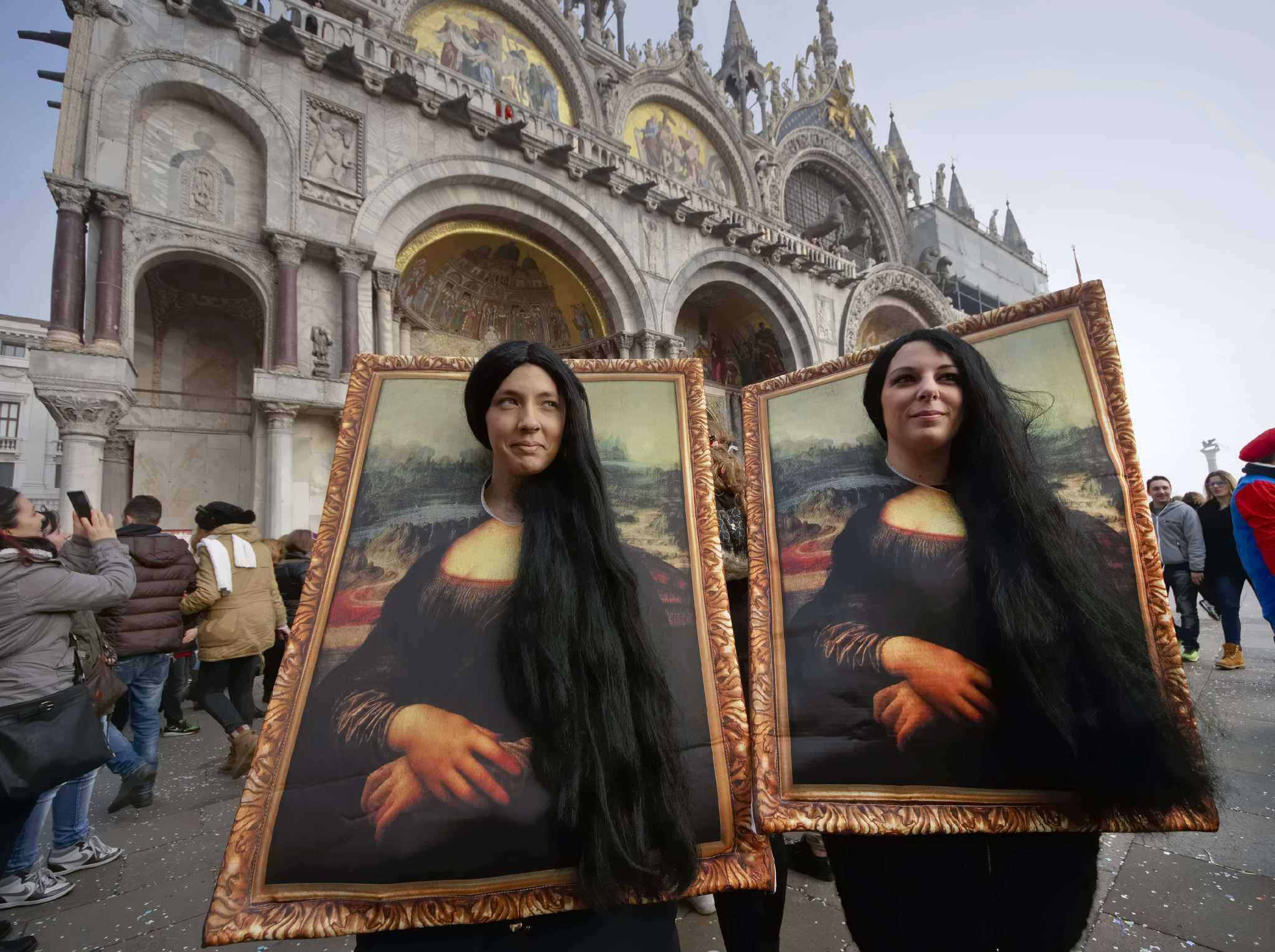 Two carnival revellers masquerade as Leonardo da Vinci's painting 'Mona Lisa' pose in St. Mark's Square in Venice, Italy, Sunday, Jan. 31, 2016. Carnival-goers in Venice are being asked by police to momentarily lift their masks as part of new anti-terrorism measures for the annual festivities. (AP Photo/Domenico Stinellis)/XDS116/211920918240/1602010028