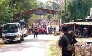 Ce document de Kawkareik Open News pris le 27 mars 2021 montre un membre armé de l'ethnie de l'Union nationale Karen (KNU) regardant des manifestants contre le régime dans l'Etat de Kayin, en Birmanie