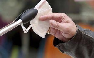 Une personne reçoit un masque FFP2 dans un supermarché de Vienne, en Autriche, le lundi 25 janvier 2021.