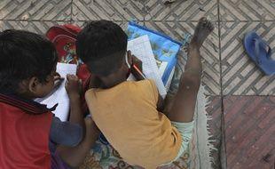 Privés d'école, deux enfants apprennent leurs leçons sur le trottoir en Inde, le 3 septembre 2020.