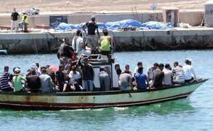Un bateau de migrants arrive sur l'île italienne de Lampedusa, le 1er août 2011. Sur le quai sont allongés les corps de 25 migrants africains qui tentaient de rejoindre l'Italie depuis la Libye.