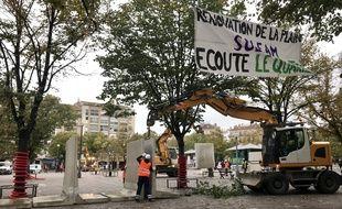 Une machine dépose les blocs de bétons sur la Plaine à Marseille.