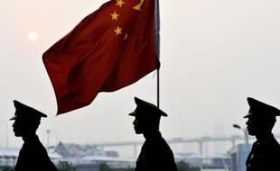 Des militaires chinois passent devant le drapeau national, le 31 octobre 2010 à Shanghai