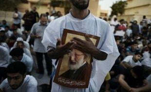 Des manifestants brandissent des portraits du cheikh Issa Qassem pour protester contre le gouvernement bahreïni qui a déchu de sa nationalité le plus haut dignitaire chiite du pays, le 20 juin à Diraz