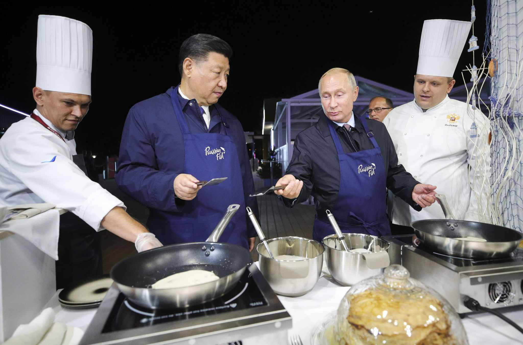 Chinese President Xi Jinping, second left, and Russian President Vladimir Putin, prepare food as they visit an exhibition during the Eastern Economic Forum in Vladivostok, Russia, Tuesday, Sept. 11, 2018.