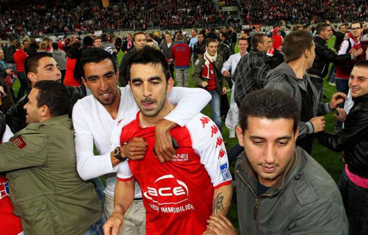 L'attaquant rémois Cédric Fauré félicité par ses supporters, le 7 mai 2012, àReims. – FRANCOIS NASCIMBENI / AFP