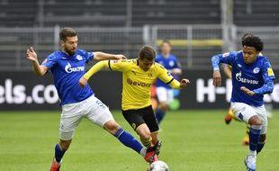 Thorgan Hazard aux prises avec le joueur de Schalke Matija Nastasic (G) lors du match de reprise de la Bundesliga entre le BVB Borussia Dortmund et Schalke 04, le 16 mai 2020 à Dortmund.