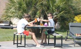 Deux enfants bien installés sur la table éco-responsable.