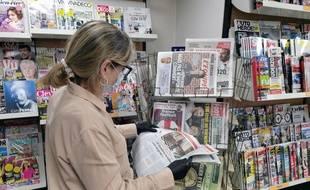 Une lectrice avec un masque et des gants qui consulte la presse.