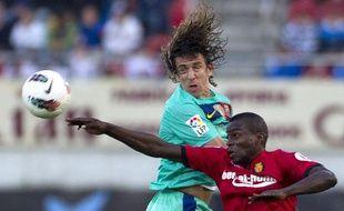 Michaël Pereira, joueur de Majorque, au duel avec le Barcelonais Carles Puyol, en mars 2012.