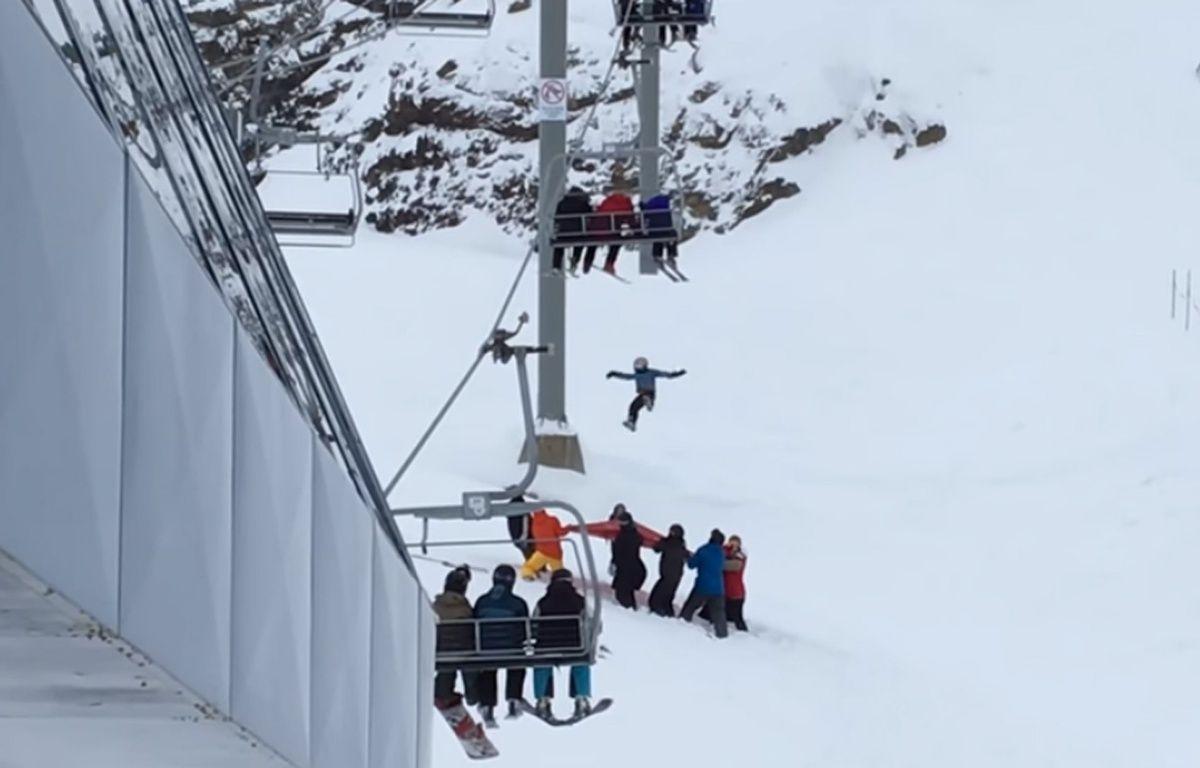 Le garçons de 11 ans est resté suspendu au télésiège 7 min, avant de pouvoir sauter sur une bâche apportée par des skieurs.  – Capture d'écran You Tube