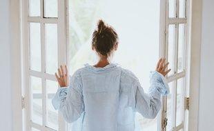 Illustration d'une femme qui aère sa chambre.