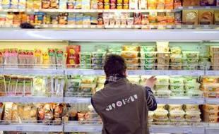 Un employé d'une grande surface devant un rayon de produits frais.