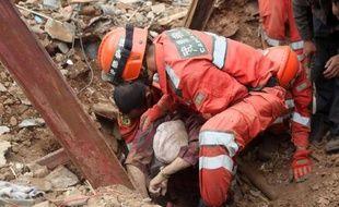 Des sauveteurs tirent des décombres un survivant, le 4 août 2014 à Zhaotong, au lendemain du séisme qui a frappé le nord-est de la province chinoise du Yunnan