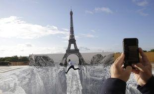 Un homme saute devant le trompe-l'œil créé par l'artiste JR devant la tour Eiffel.