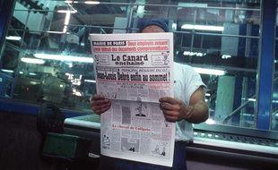 Dans une imprimerie, un ouvrier lit le journal satirique «Le Canard enchaîné».