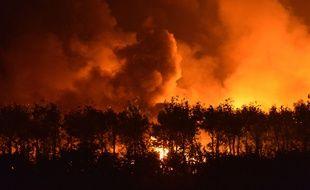 Des flammes et de la fumée s'élèvent du site où  a eu lieu une série d'explosions le 12 août 2015 à Tianjin, en Chine.
