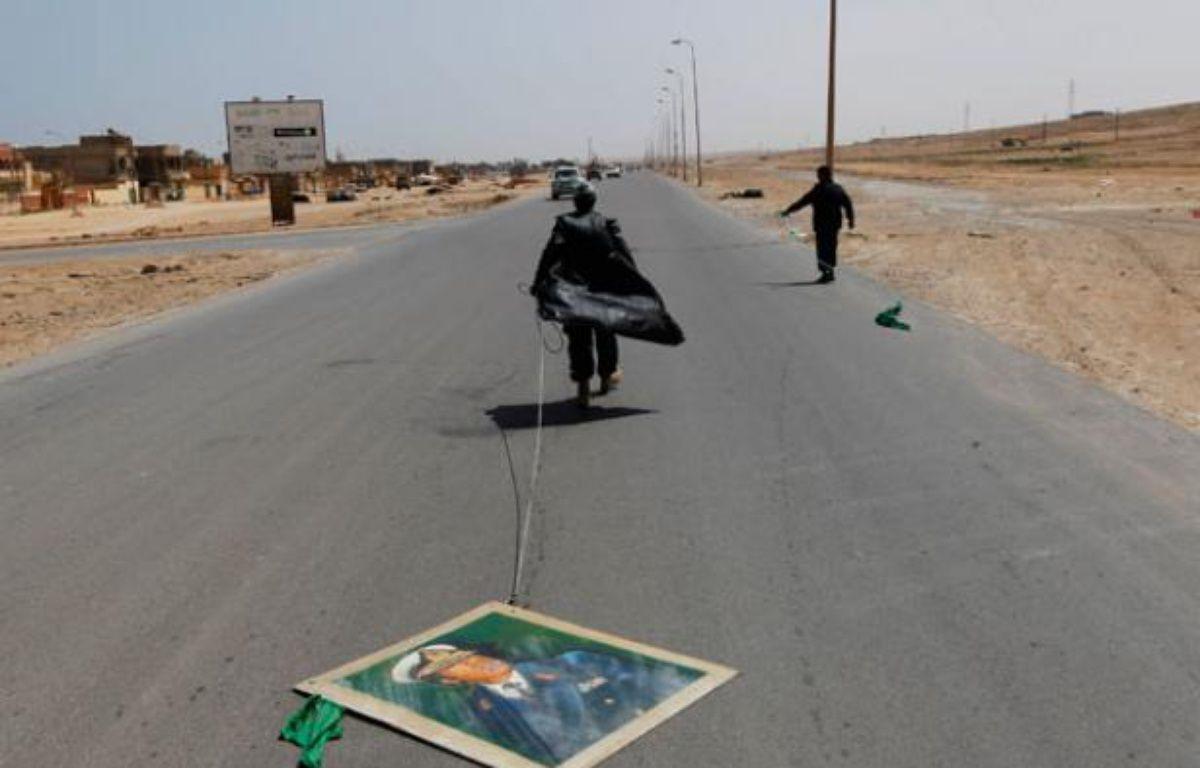 Un rebelle traine un portrait du leader libyen Mouammar Kadhafi sur une route à Bin Jawad, Libye, le 28 mars 2011. – Y. BOUDLAL / REUTERS