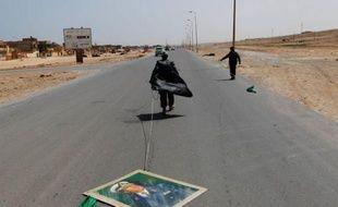 Un rebelle traine un portrait du leader libyen Mouammar Kadhafi sur une route à Bin Jawad, Libye, le 28 mars 2011.