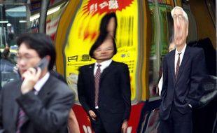 Des «salarymen» japonais reflétés dans une vitrine à Tokyo.