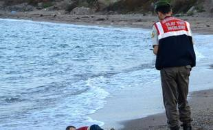 Un policier turc se tient près du corps d'un enfant migrant mort noyé, sur une plage de Bodrum, au sud de la Turquie, après le naufrage d'un bateau transportant des réfugiés, le 2 septembre 2015