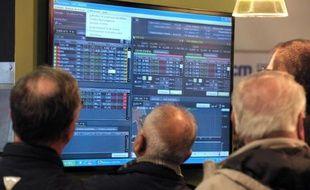 Des personnes regardent les cours de la Bourse sur un écran