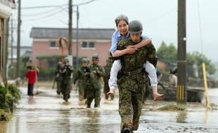 Les soldats japonais aident les résidents à évacuer les zones inondées de la ville d'Asakura, dans la préfecture de Fukuoka au Japon, le 6 juillet 2017.